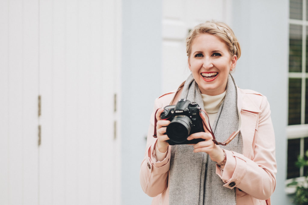 woman holding a camera during her personal brand photoshoot in london