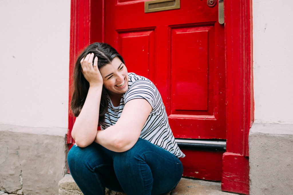 woman laughing in front of red door in oxfordshire personal brand photoshoot
