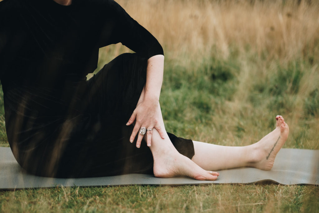 Close up image of a woman in a seated twist outside