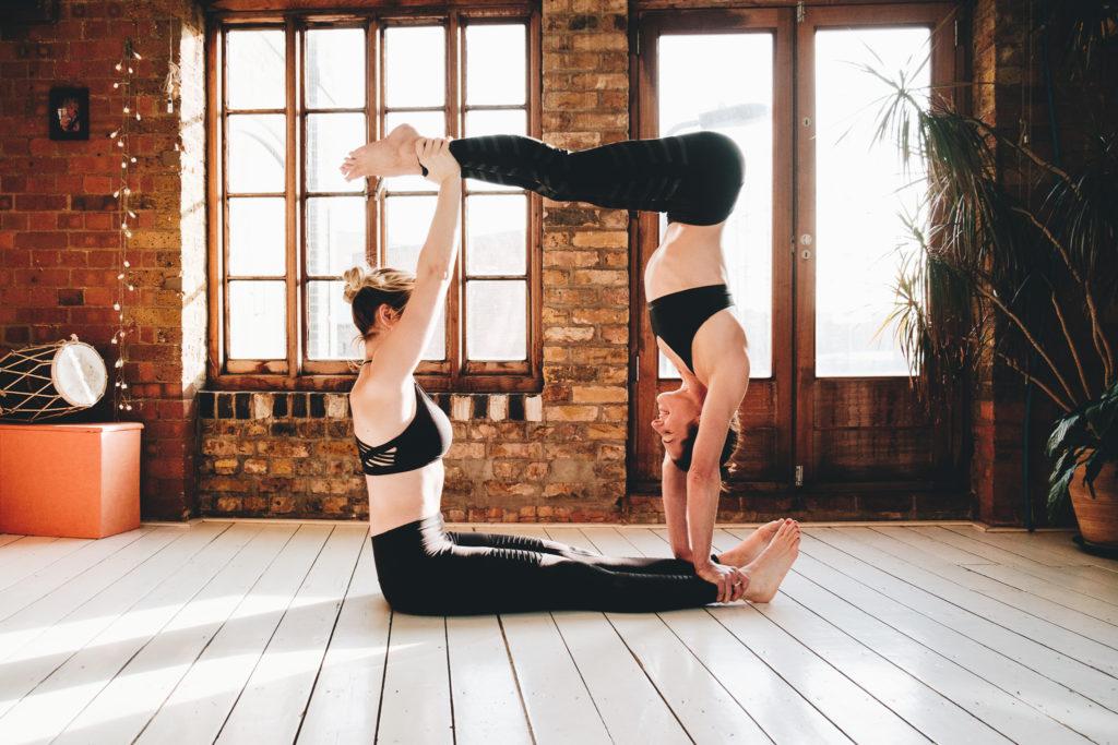 Partner yoga of two women in a box shape