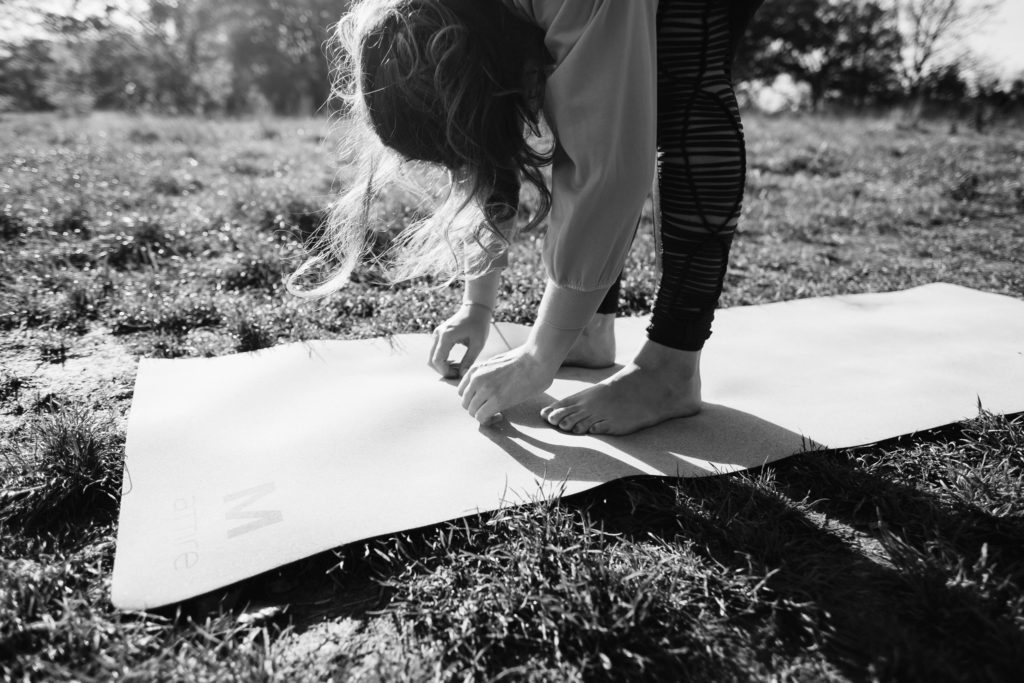 Black and white image of a woman in a forward fold on a yoga mat