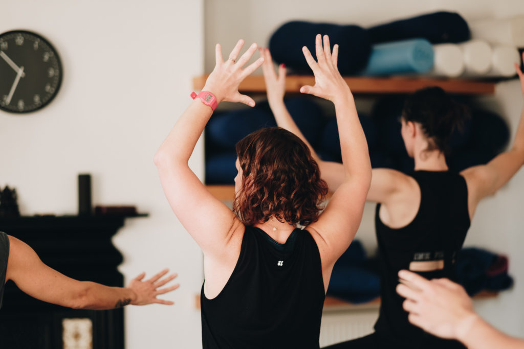 a yoga class with arms out wide